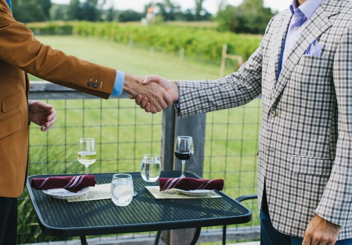 Two local business owners shaking hands over a meal on the balcony of our primary dining space at Farmer and Frenchman Winery.